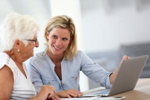 Vrouw helpt oudere vrouw bij digitale zaken