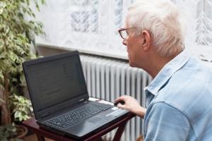 Oudere man achter de laptop bekijkt zijn bereichtenbox