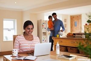 jonge moeder zit achter laptop en doet aangifte inkomstenbelasting