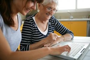 jonge vrouw helpt oudere vrouw bij het bekijiken van haar digitale post