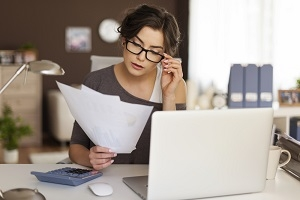jonge vrouw doet achter laptop aangifte inkomstenbelasting