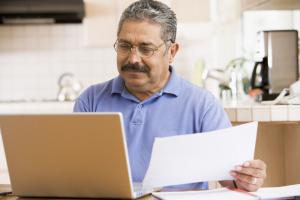 Meneer leest zijn post van de Belastingdienst zowel digitaal als op papier